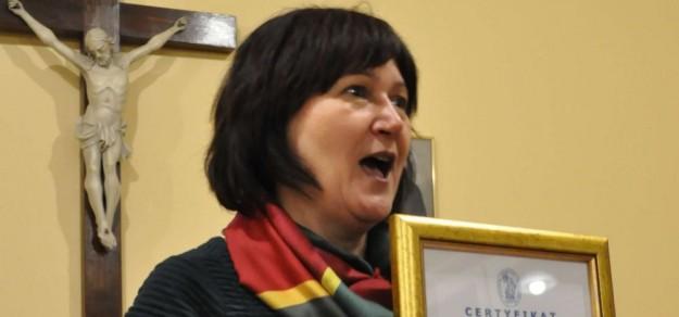 Teresa Buczak, prezes Hospicjum Ojca Pio prezentuje Certyfikat ISO:9001:2015, który przyznano pszczyńskiemu hospicjum (fot. Hospicjum św. Ojca Pio)